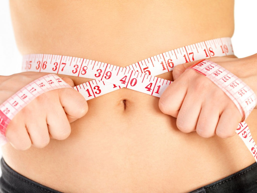 Femme qui se mesure le tour de taille.