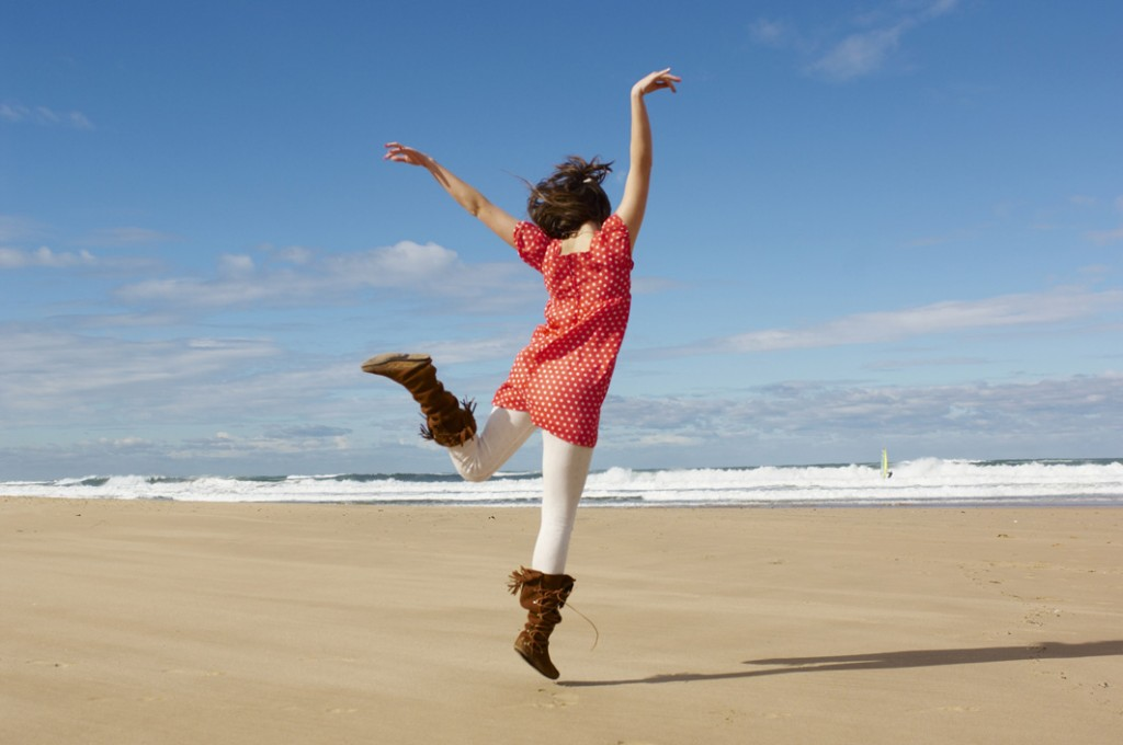 Jeune fille qui danse sur la plage en hiver. Impression de bien-être.