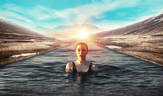 Femme sportive dans l'eau entourée d'un paysage naturel.