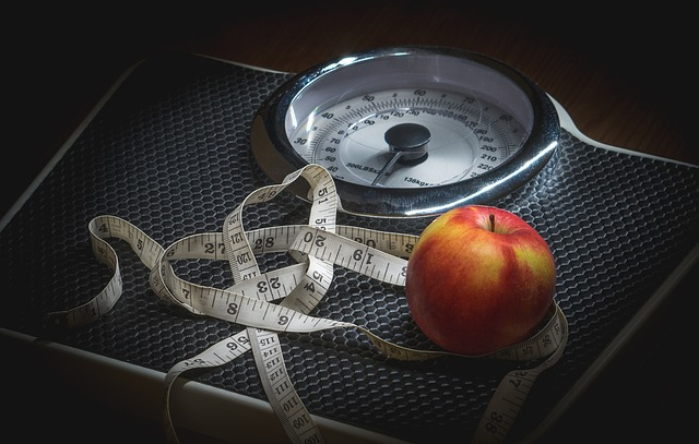 Un mètre et une pomme posés sur une balance.